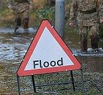Warning sign: flooded area. Soldiers helping the local authorities.